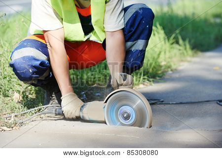 Builder worker with cut-off machine power tool breaking asphalt at road construction site poster