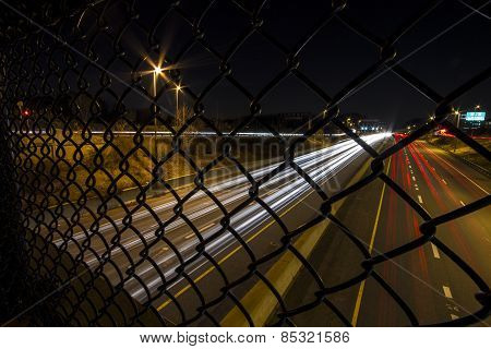Long exposure of highway at night as seen from the walkway above through a chain link fence. The road is Interstate 270 in Bethesda, MD. poster