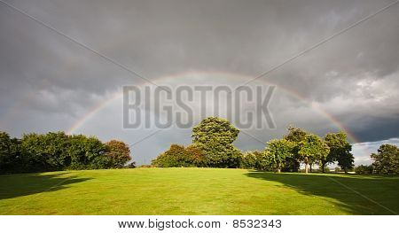 Rainbow Over An Orchard In Summer