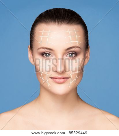 Portrait of young, beautiful and healthy woman with arrows on her face (spa, plastic surgery, face lifting and make-up concept)