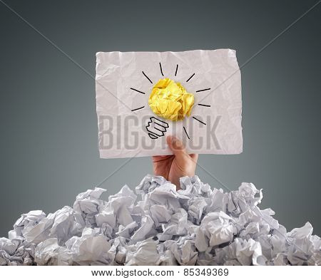 Businessman buried under crumpled pile of papers with an idea sign