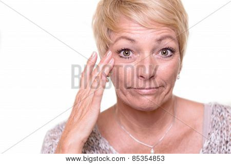 Attractive Senior Blond Woman Checking Her Complexion