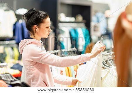young woman choosing which dress wear