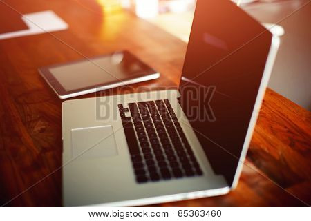 Workplace with open laptop with black screen and digital tablet on modern wooden desk