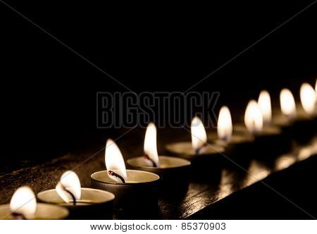 Lit candles in a row at night