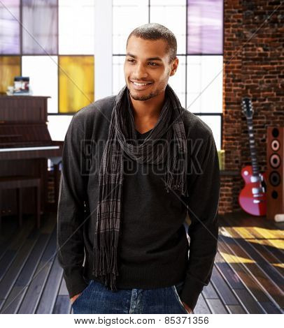 Portrait of happy casual bristly afro american musician at home studio. Standing, smiling, hands in pocket.