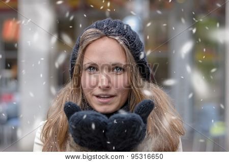 Young Woman Blowing Snow At The Camera