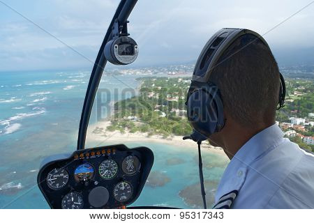 Inside Helicopter, Pilot In Seat Over Tropical Landscape