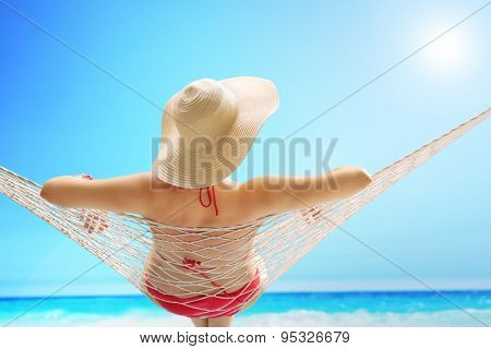 Rear view of a woman in a red swimsuit with a stylish hat lying on a hammock on a beach by the sea