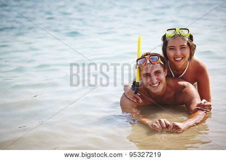 Affectionate scuba divers lying in water