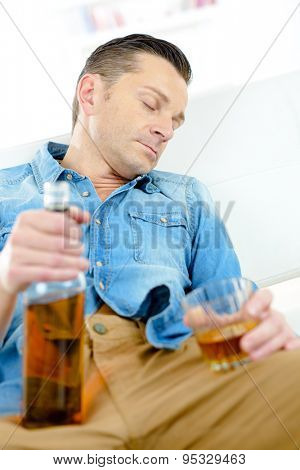 Man asleep holding bottle and glass