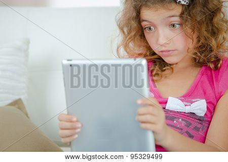 School girl with shocked expression, looking at tablet