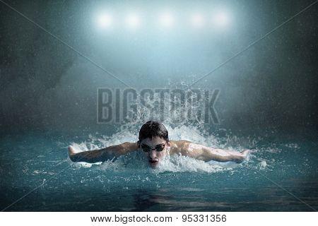 Swimmer in waterpool. Butterfly style.
