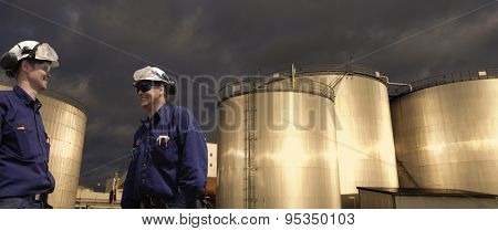 oil and fuel workers with giant storage tanks, sunset in late evening