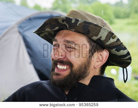 Portrait of a smiling bearded man in a broad-brimmed hat in the street.