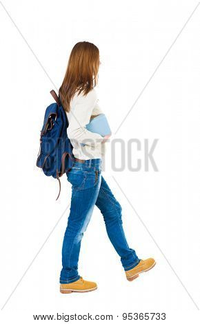 Girl with a backpack on his back is a stack of books. back view. Rear view people collection.  Isolated over white background. A girl in a white blouse with a blue backpack carries book under his arm