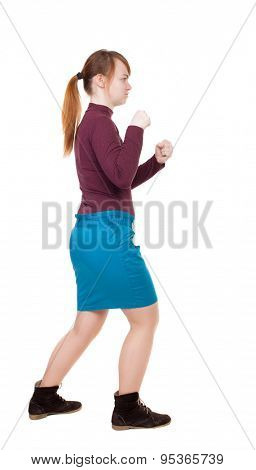 skinny woman funny fights waving his arms and legs. Rear view people collection.  backside view of person. Isolated over white background. girl in a blue skirt and a burgundy sweater fights with fists