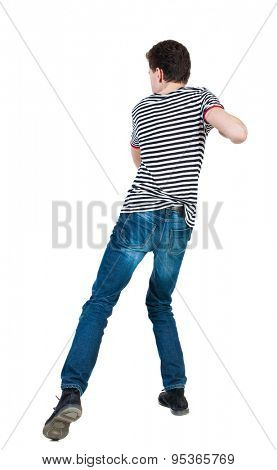 back view of skinny guy funny fights waving his arms and legs. Isolated over white background. backside view of person. Funny guy clumsily boxing. The guy in the striped shirt in the backswing.