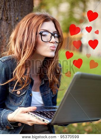 education, flirting, distant relationship, virtual communication and love concept - happy student girl with laptop computer sending air kiss at campus