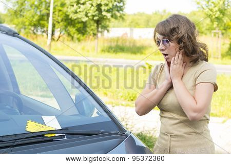 Suprised woman looking on parking ticket placed under windshield wiper