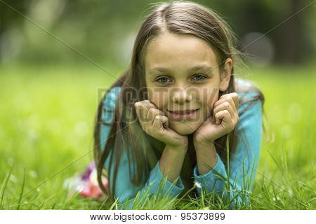 Close-up portrait of a nine year old girl lying in the green grass.