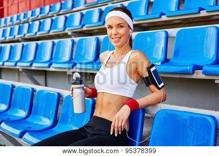 Happy girl in activewear looking at camera at stadium