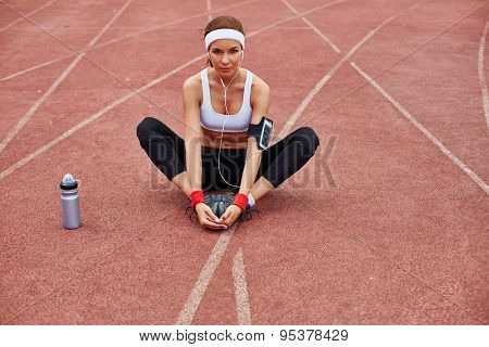 Young sporty woman in activewear sitting at stadium