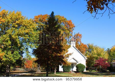 Beautiful small church nestled in autumn trees