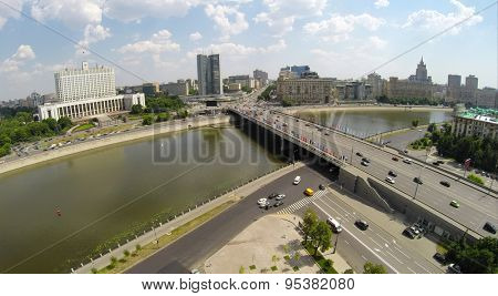 RUSSIA, MOSCOW - JUN 6, 2014: Cars ride by bridge and quay near White House. Photo with noise from action camera