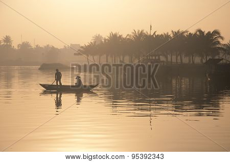 Two people on boat on Hoai river in Hoian, Vietnam