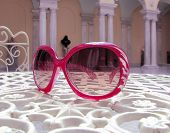 A pair of pink sunglasses sitting on an Italian cafe table with columns in the background. poster