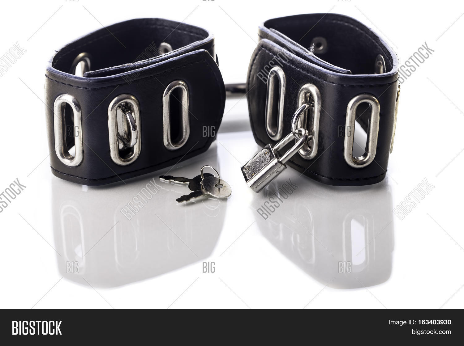 Leather bondage handcuffs for sex fetish and sexual role play. Image  isolated against white background