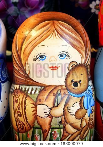 Matrioska representing a young girl with a toy bear. On sale in a christmas street market.