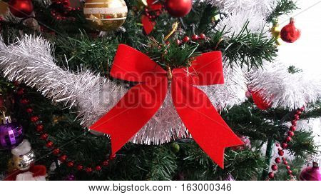Red bow, silver chain and other ornaments on the Christmas tree