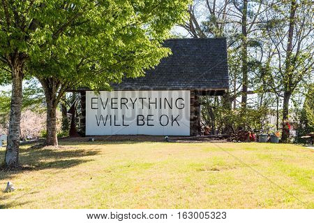 A sign saying everything will be ok on an old barn