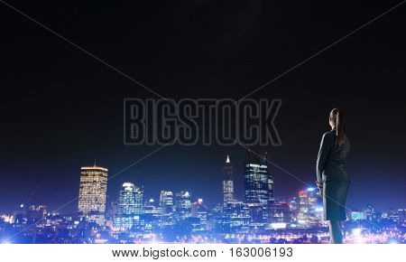 Rear view of elegant businesswoman viewing lights of night city