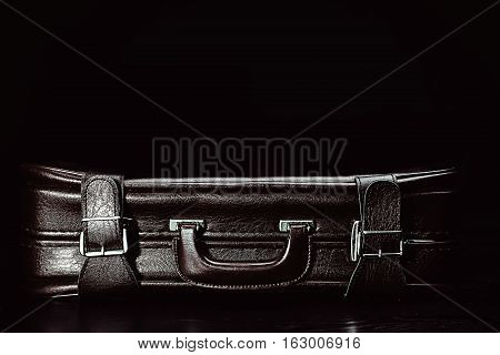 stylish brown leather suitcase in black background