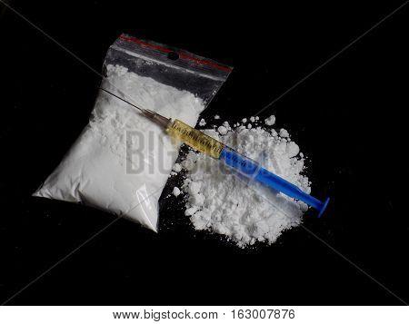 Injection syringe on cocaine drug powder bag and pile on black background