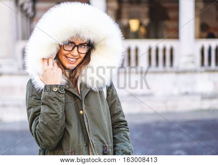 Happy young girl in winter clothes wearing glasses smiling at camera - Stunning woman in winter coat with fur hat in the city center during a cold day - Beauty and fashion concept