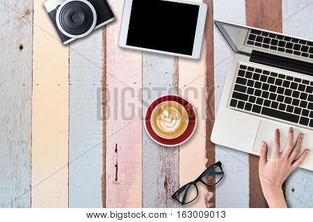 Bussiness work desk with laptop camera cup of coffee put on colorful wooden table