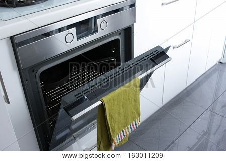 Opened oven with green cloth hanging on it