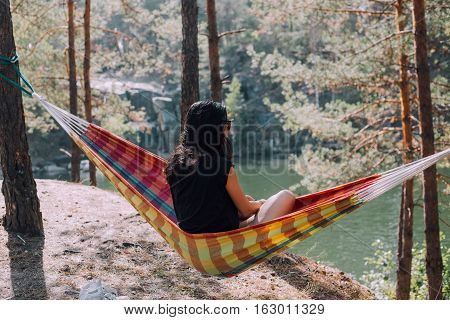 girl resting in a hammock in the woods camping in a hammock. Healthy lifestyle in the forest.