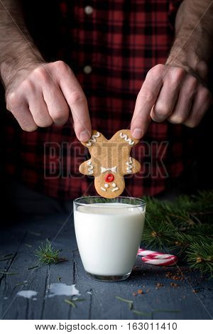 Male hands holding gingerbread man cookie above the glass of milk. Christmas holidays, winter, New Year concept. Fun with food.
