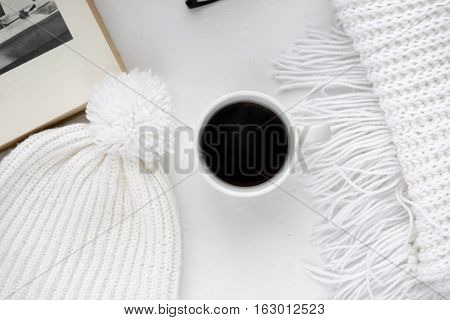 Handmade knitted wool scarf and cap. Winter clothes. Hot coffee cup on wooden background. Concept cozy atmosphere with a cup of coffee in winter. Top view