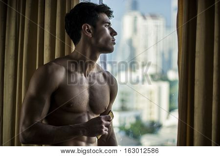 Sexy handsome young man standing shirtless holding a cell phone, in his bedroom next to window curtains