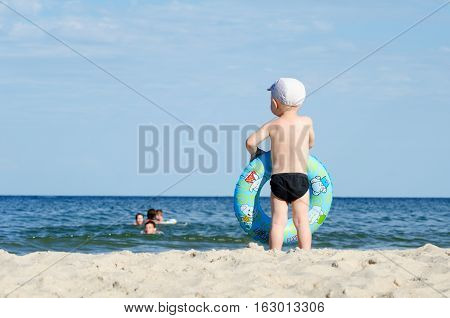 Kid in swimming trunks and a cap with a swimming circle stands on the shore of the sea back people swim away