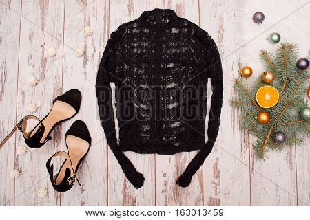 Guipure blouse and black shoes on a wooden background Christmas balls on fir branch. Fashionable concept top view