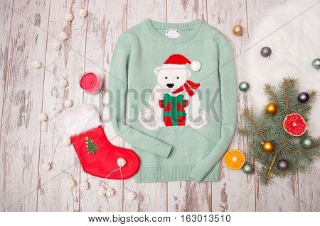 Green sweater with a bear on a wooden background. Fir-tree branch with Christmas decorations stocking gift