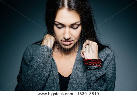 Close-up portrait of a sad and depressed woman model with long beautiful hair eyes down. Indoor studio photosession.