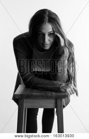 Beautiful attractive girl with perfect long hair thinks. Fashion black and white photoshoot.